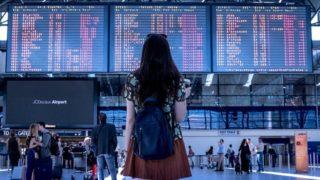 空港の発着時刻表を見上げる女性